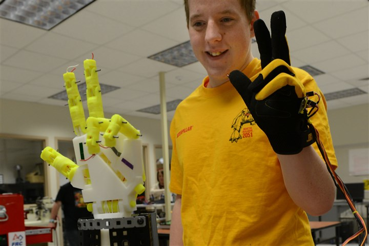 "glovehand Alex Burns gives a ""V"" sign with his hand using a glove with flexible sensors at A.W. Beattie Career Center. Alex's hand was made with a 3-D printer."