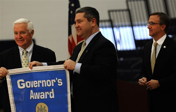 20130114ppGovaward3SOUTHLOC.1 Pennsylvania Gov. Tom Corbett congratulates Mt. Lebanon High School principal Brian McFeeley with a Governor's Award of Excellence as superintendent Timothy Steinhauer looks on during an assembly on Tuesday at the school.