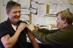 Greg Robes gives Tim Flanigan, 55, of Baldwin, a flu shot earlier this year at the Allegheny County Health department's vaccination clinic in Oakland.