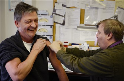 20140115jrFluLocal Nurse Greg Robes gives Tim Flanigan, 55, of Baldwin a flu shot Wednesday afternoon at the Allegheny County Health Department's vaccination clinic in Oakland.