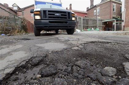Pothole in Bloomfield Vehicles inch through potholes on Comrie Way near Pearl Street in Bloomfield earlier this year.