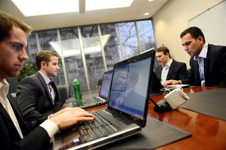 Business students University of Pittsburgh students, from left, Sean Yeager, Andy McClaine, James Founds and Harris Vuadens analyze the value of PPG, part of an annual Chartered Financial Analyst Institute contest.