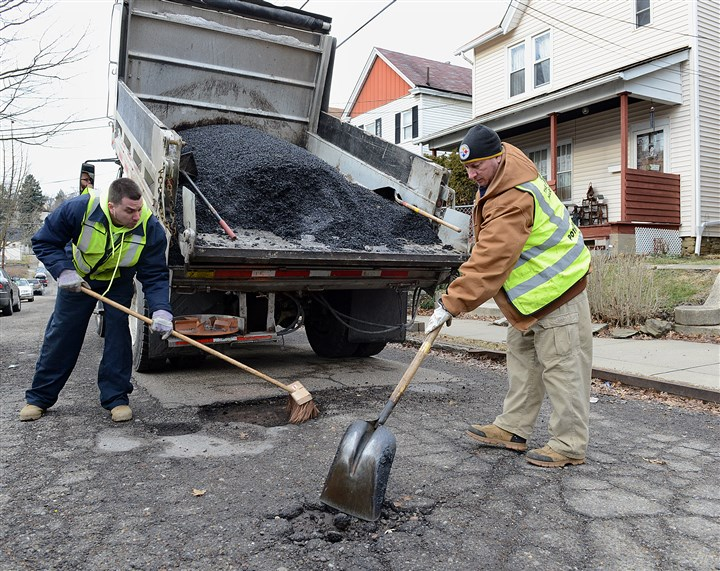 "Pothole filling on ""blitz"" day Justin Mazurek, left, and Eric Thomas fill potholes with asphalt cold patch yesterday on Sutherland Street in Sheraden. In the first full day of Mayor Bill Peduto's pothole ""blitz,"" public works employees worked to clear the 149 complaints logged the first 13 days of this year."