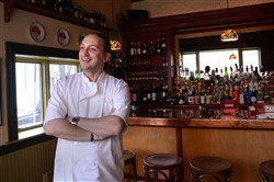 Chef Michele Savoia stands in front of the bar at Dish Osteria and Bar on South 17th Street in the South Side in 2014.