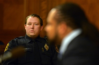 Gromek listens to Henderson testify with CPRB Pittsburgh Police Officer Jonathan Gromek, left, listens to Dennis Henderson, right, a teacher from the North Side.