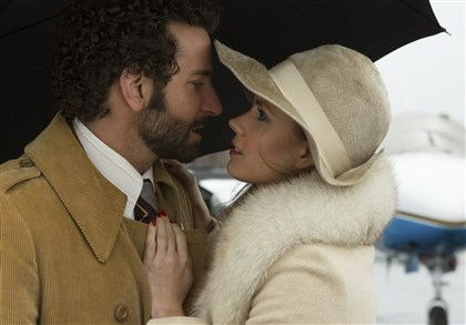 "AMERICAN HUSTLE From left, Richie Dimaso (Bradley Cooper) and Sydney Prosser (Amy Adams) embrace each other on the in Columbia Pictures' ""American Hustle."""