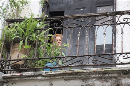 20140117psCubaSeen2-6 A curious woman peers out of her small home in Havana, Cuba.