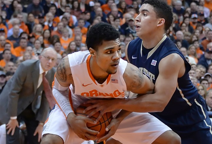 Pitt's James Robinson; Syracuse's Michael Gbinije Syracuse' Michael Gbinije pulls down a rebound against Pitt's James Robinson in the first half.