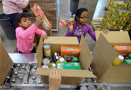 20140120radMLKingFoodBankLocal01-2 Alexandria Graves, 8, left, and Marcia Hill, 9, were among the 120 volunteers and their families from Sam's Club, Jack and Jill, Pittsburgh Cares and the Garden of Peace project packing 2,600 supplemental food boxes for seniors Monday at the Greater Pittsburgh Community Food Bank in Duquesne.