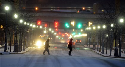 Snow scene Commuters cross General Robinson Street on the North Side during the predawn snow.