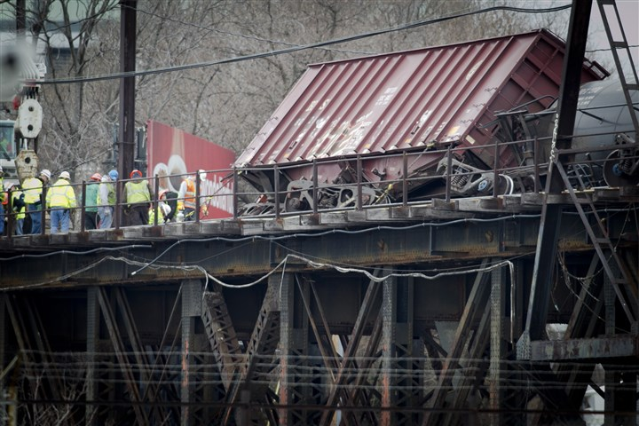 Philadelphia train derailment A box car sits on its side as workers prepare to set it upright.