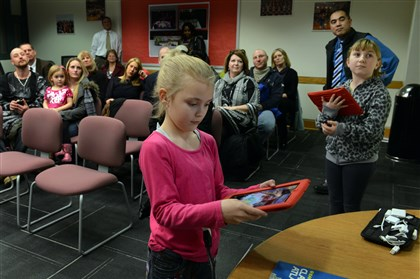 20140115bwDreamBus04-1 Kyleigh Fetchen, 8, and Cassidee Fitterer, 9, right, both of Forward, show their third-grade class video from their own school iPads during an Elizabeth Forward School District board meeting during which the district was recognized as an Apple Distinguished Educators Program.