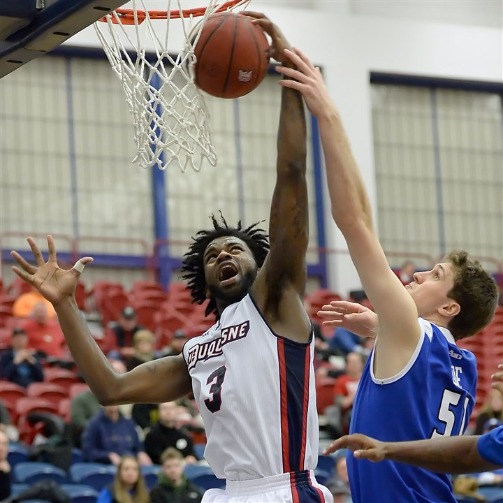 mckoy0201 Duquesne's Dominique McKoy is fouled by Saint Louis' Rob Loe in the second half at Palumbo Center Wednesday night.