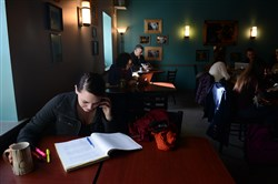 Indiana University of Pennsylvania senior Amy Haller, 21, of Bellevue, left, studies with a friend over the phone at Commonplace Coffee in Indiana, Pa.