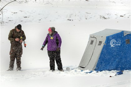 Ice fishing on North Park Lake 01 As the snow falls at North Park Lake on Thursday, Lena Merlino, right, of Ross, discusses the placement of tip-ups for an afternoon of ice fishing with her friend Mike Boyza of Centerville.