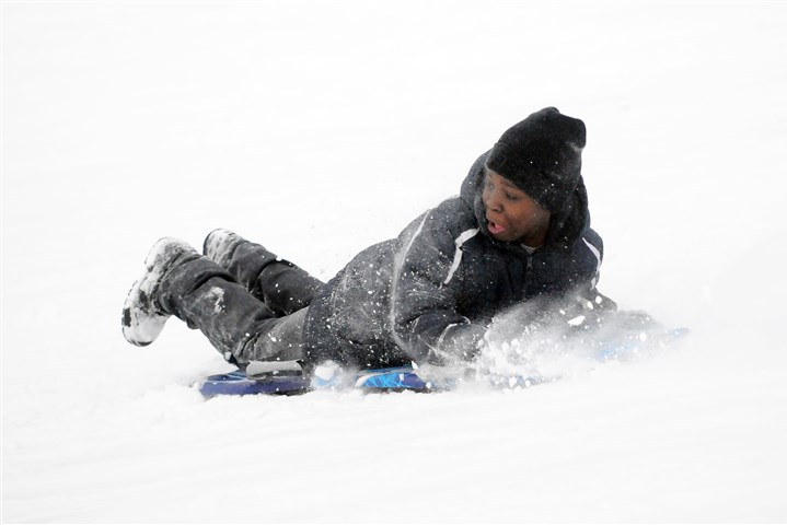 Sledding in Schenley Park Kamaal Thompson of Greenfield sleds backwards down a hill in Schenley Park.