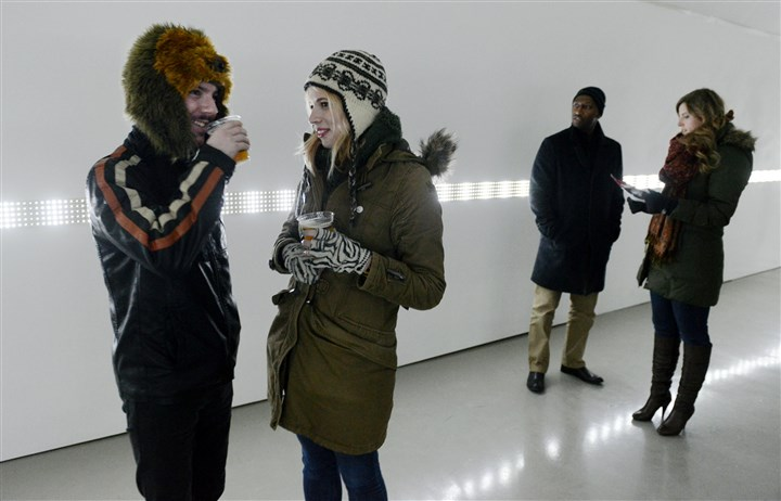 Cold weather at the Gallery Crawl Mike Schmitt of Squirrel Hill, left, and Claire Sullivan of Shadyside in the Wood Street Galleries showing light installations by Austrian-born artist Erwin Redl. They are part of the crowd that braved cold temperatures Friday night for the Pittsburgh Cultural Trust Gallery Crawl at various locations Downtown.