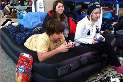 Waiting for tickets Students Josh Korber, Melinda Black and Sarah Vansow relax on an air mattress awaiting tickets to go on sale for tonight's Pitt-Duke basketball game. They arrived at 11:30 last night.