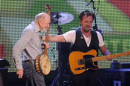 Obit Seeger Pete Seeger, left, is welcomed on stage by John Mellencamp during the Farm Aid 2013 concert in Saratoga Springs, N.Y.