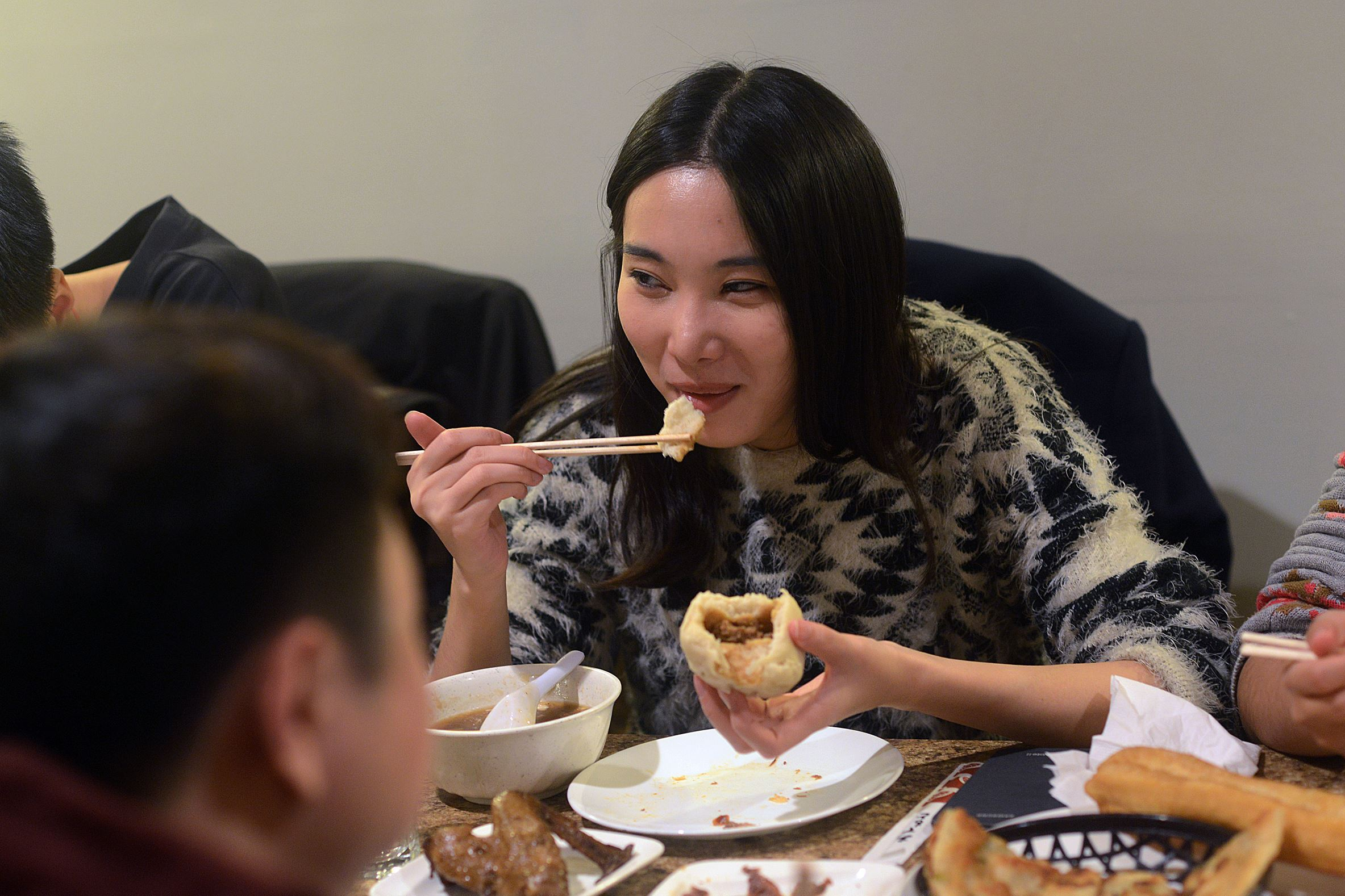 Chinese New Year food Di Zhang, center, eats a steamed bun at breakfast at Sakura, in Squirrel Hill.