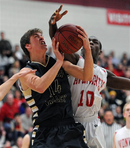 hsgame1 Quaker Valley's Tyler Garbee has his shot blocked by Avonworth's Jamal Hughley in first half action.