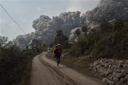 9mj00m0e-1 A resident runs to escape a cloud of hot volcanic ash that engulfed several villages in the Karo district of Indonesia during the eruption Saturday of Mount Sinabung volcano on Sumatra island. Fourteen people, including four schoolchildren, were killed after the volcano's biggest eruption in recent days.