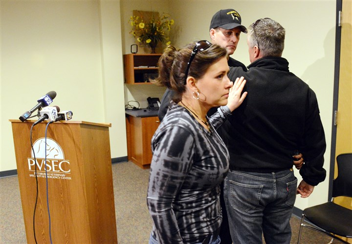 20140130bwRocLocal02 Staff surgeon Julie Compton, left, of the Pittsburgh Veterinary Specialty & Emergency Center offers a comforting touch to Pittsburgh police K-9 Officer Tim Crane, who is talking to fellow K-9 Officer Dan Tice, after it was announced that Rocco, a K-9 officer and German shepherd, had died as a result of an injury sustained while apprehending a suspect.