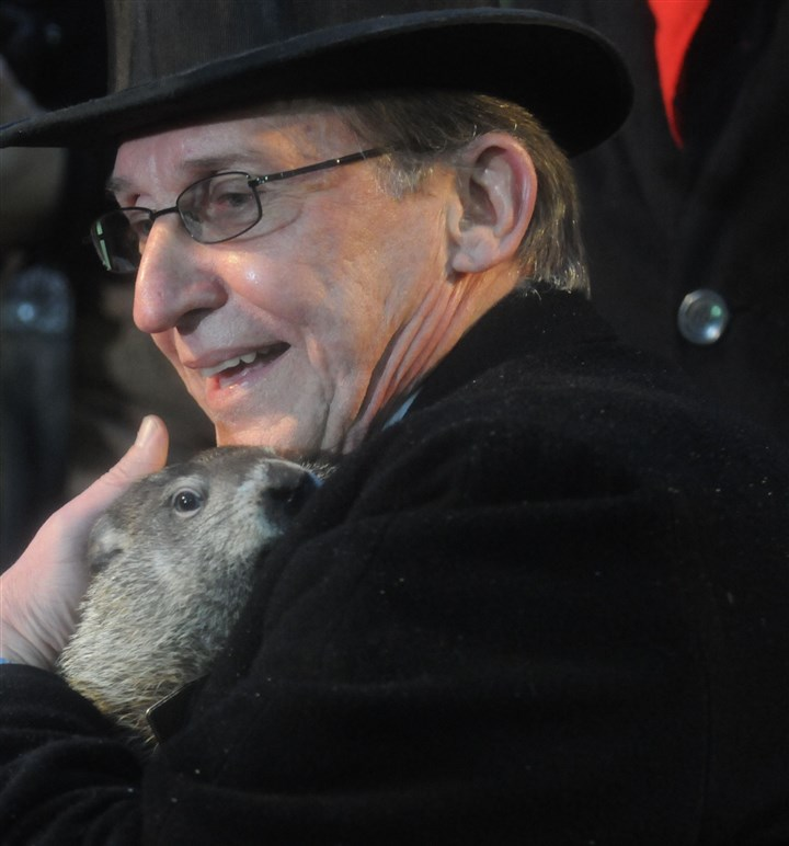 Punxsutawney Phil and handler Punxsutawney Phil's handler Ron Ploucha holds him close early this morning.