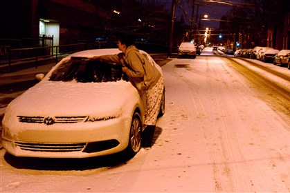 Snowy Monday Morning Sara Zamlotti of the South Side, clears snow from her car along Sarah Street before dawn on Monday.