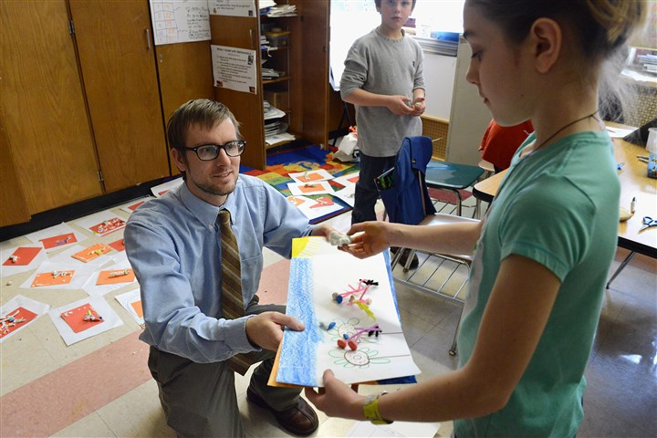 STAR school Whittier K-5 Fourth-graders turn in art projects to Whittier K-5 art teacher Brian Bolchko.