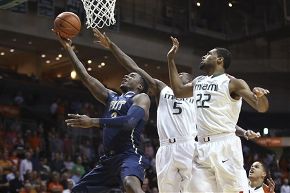 Pittsburgh Miami Basketball Pitt's Michael Young slides past Miami's Davon Reed and Donnavan Kirk for two points during the first half.