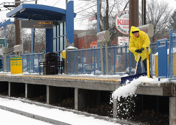 20140205radWeatherIceLocal0.1-15 A Port Authority worker shovels snow and ice from an empty Lytle Station platform Wednesday on the Blue Line-Library train line. Early morning ice disrupted service on the Port Authority's Red and Blue lines in the South Hills.