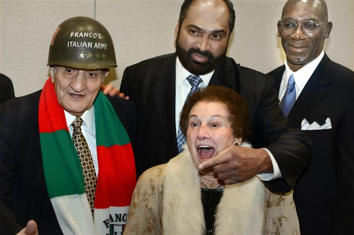 20140206bwDapperSpts03cc-1 Pointing to a photographer, Franco Harris, honored with the Lifetime Achievement Award at the 78th Annual Dapper Dan Dinner & Sports Auction, poses with 86-year old Al and Rita Vento, 91, of Whitehall. Mr. Vento was one of the original Franco's Italian Army Generals. John Stallworth, at right, is another Steelers great.