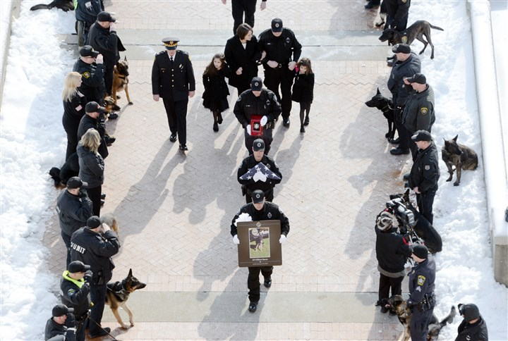 Rocco funeral in Oakland, with urn (corrected) Rocco's funeral procession moves into Soldiers & Sailors Memorial Hall in Oakland. The third officer from the front is carrying an urn with the cremated remains of the canine officer.