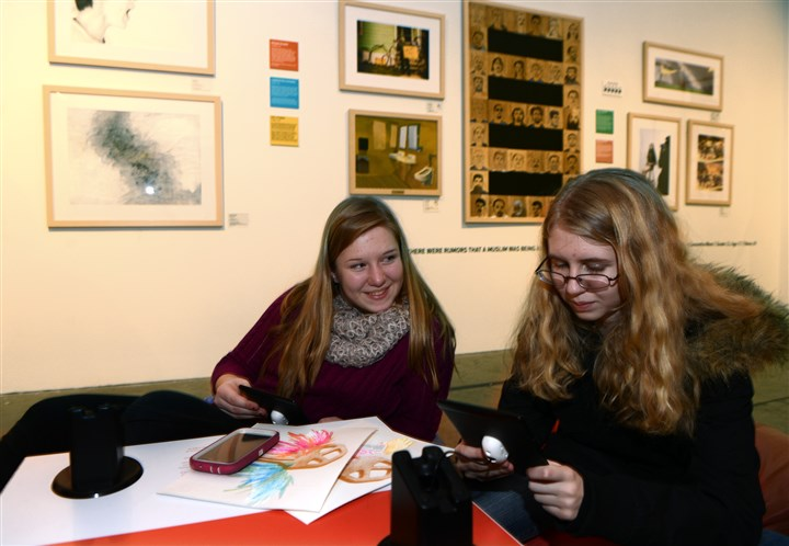 2013 Scholastic Art & Writing Awards Vanessa Anthony, left, and Leah Fulton, both 14 and ninth graders at North Allegheny Intermediate High School, read stories in the Art.Write.Now.Tour exhibition at the 2013 Scholastic Art & Writing Awards at The Andy Warhol Museum.