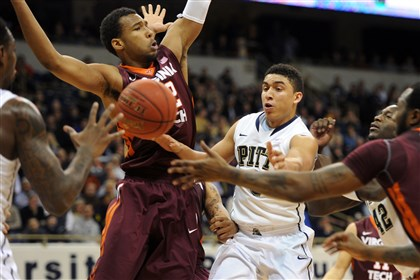 20140208ppPittVaTech2SPORTS-1 Pitt guard James Robinson passes off under tight defense by Virginia Tech during Pitt's overtime win at Petersen Events Center.