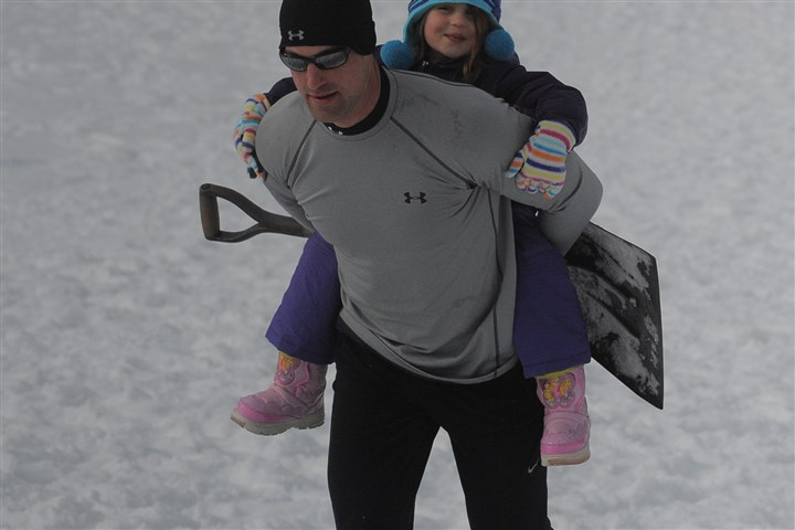 Snow shovel 2 Jim Neese of Marshall carries his daughter Emma Neese, 4, up the hill after Emma rode her shovel.