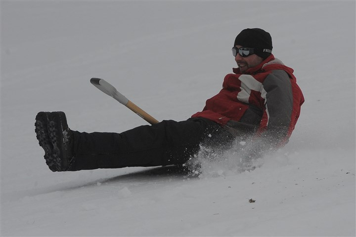 Snow shovel Adam Black of Chippewa rides his shovel down the hill at the annual snow shovel riding competition at Old Economy Park in Beaver County.