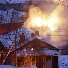 Fire in Swissvale  A firefighter cuts holes in a roof of one of the homes ablaze Thursday morning in Swissvale.