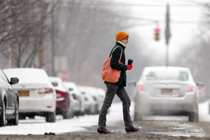 NY Winter Weather Upstate NY A woman walks along snowy Lark Street on Thursday morning in Albany, N.Y. A winter storm is bringing heavy snow to locations along the East Coast, including parts of Pennsylvania.