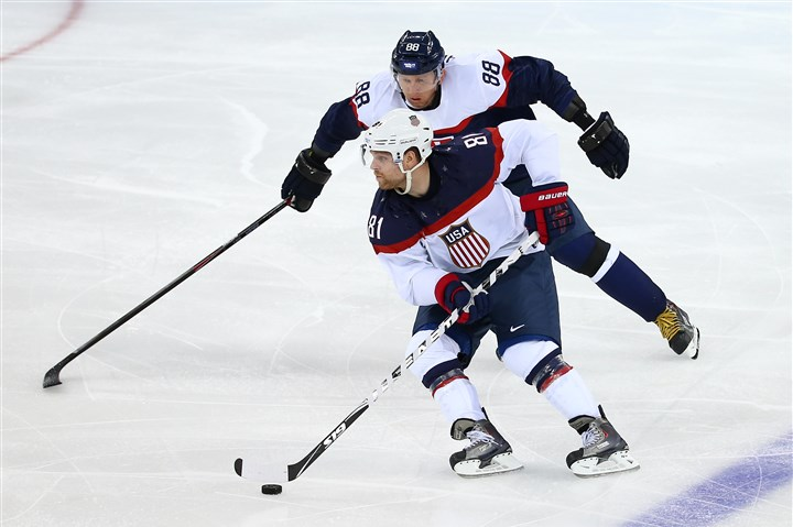 U.S. hockey Phil Kessel, front, of United States and Marcel Hossa of Slovakia battle for the puck Thursday at the Sochi 2014 Winter Olympics.