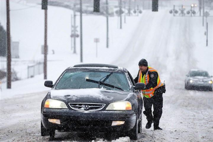 Winter Weather NC Greensboro, N.C., police officer A.R. Schoonmaker pushes a car, which became stuck on a hill during the heavy snow yesterday. The winter storm today is pushing into Pennsylvania.