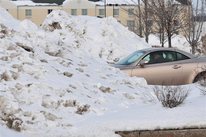 WinterWeatherPa A couple enters the Walmart parking lot yesterday between two massive snow piles in Wilkes-Barre. A winter storm is expected to drop even more snow today.
