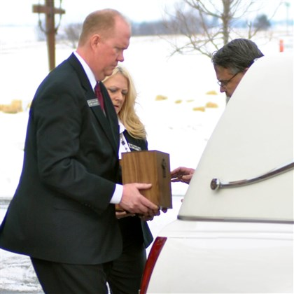 Wolfe sisters funeral 02 Lemke Funeral Home directors deliver the cremated remains of Susan and Sarah Wolfe to a hearse.