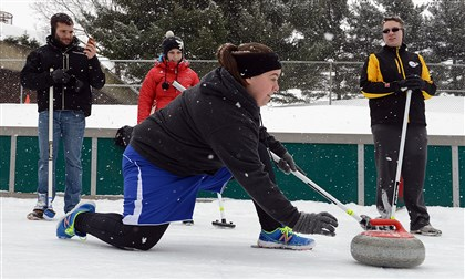 20140215radCurlingLocal03-2 Marci Pursglove of Ohio Township slides on her left foot as she learns to cast the stone Sunday during the Pittsburgh Curling Club's workshop at Schenley Park's ice rink.