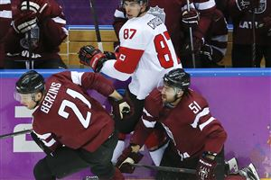 Latvia forward Armands Berzins and forward Koba Jass collide with Canada forward Sidney Crosby during the second period of a men's quarterfinal ice hockey game at the 2014 Winter Olympics, Wednesday, Feb. 19, 2014, in Sochi, Russia. Canada won 2-1.