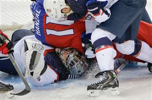 USA goaltender Jonathan Quick is crushed under Czech Republic forward Martin Hanzal during the third period of men's quarterfinal hockey game in Shayba Arena at the 2014 Winter Olympics, Wednesday, Feb. 19, 2014, in Sochi, Russia.