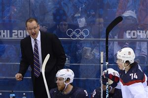 US' coach Dan Bylsma (L) talks to his players during the Men's Ice Hockey Quarterfinals match between the USA and the Czech Republic at the Shayba Arena during the Sochi Winter Olympics on February 19, 2014.
