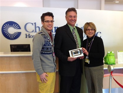 Kevin Sergent of Tri-Star Auto Group at Children's Hospital Pictured in the center is Kevin Sergent, principle owner of the Tri-Star Auto Group flanked by Matthew Brooks and Sandy Clement of the Child Life Department of Children's Hospital of Pittsburgh of UPMC. Tri-Star donated 13 computer tablets to the Child Life Department.