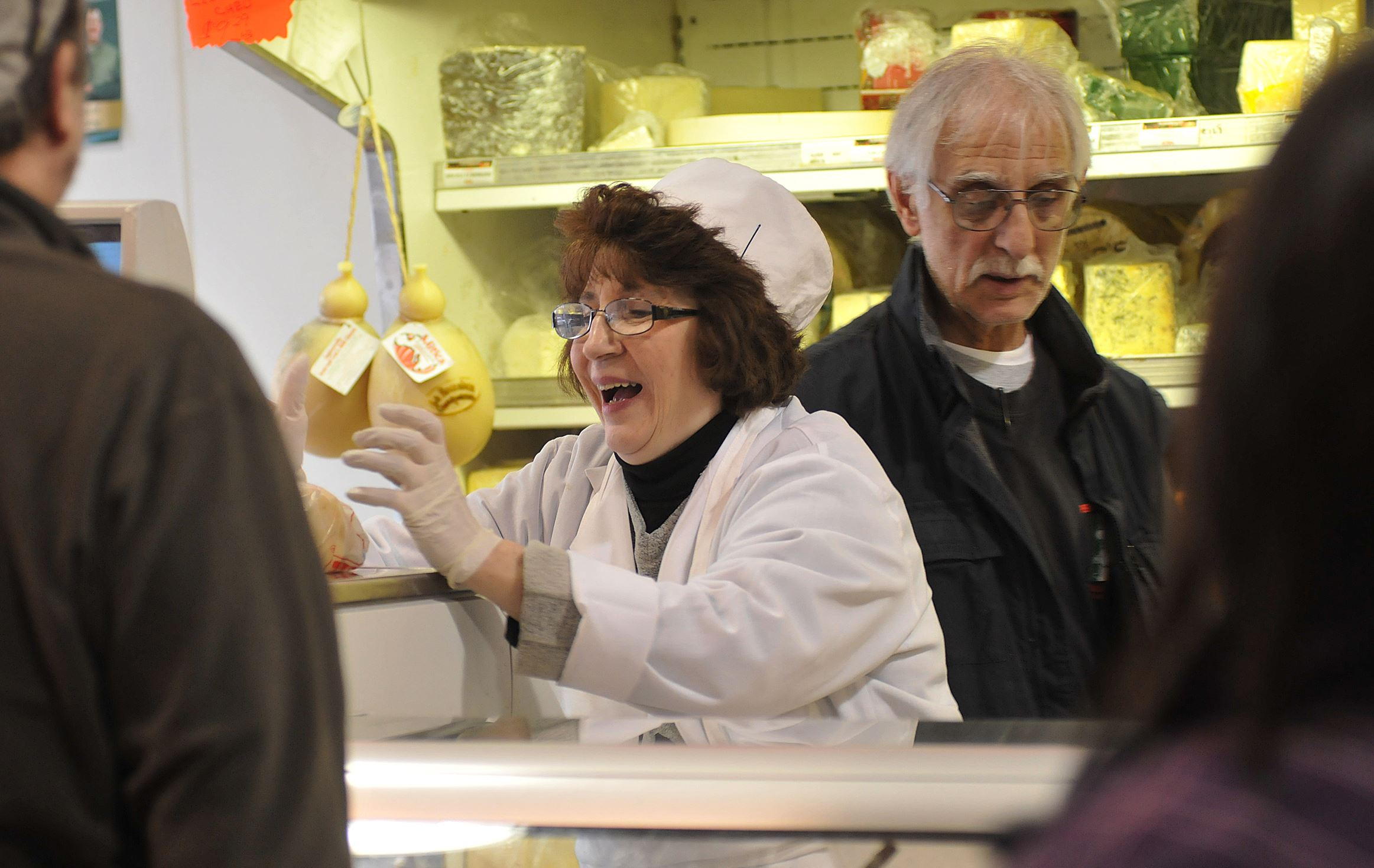 Dearheart sale Carol Pascuzzi, cheesemonger at Penn Mac since 1984, weighs a piece of cheese for a customer. At right is cheesemonger Nick Pascuzzi, Carol's husband.